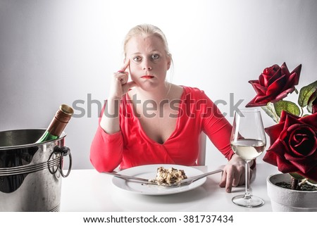 Over eating concept - Eating too much  - Woman in red dress had too much to eat - Eating and drinking too much - Diet and dieting concept - Eating healthy - Alcoholism - Gluttony - Desire and appetite - stock photo