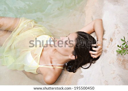 Over head beauty view of an attractive young woman laying on the shore of a spa natural swimming pool submerged in clear waters and relaxing while on a summer holiday. Beauty and healthy lifestyle. - stock photo