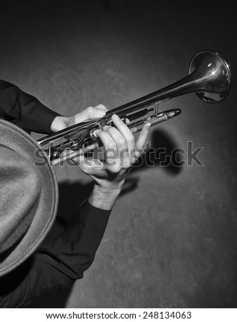 Over head black & white image of man in fedora playing trumpet.