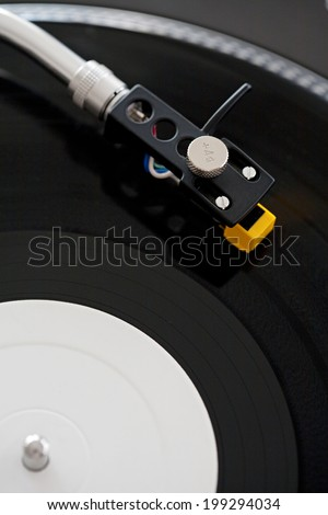 Over head close up detail view of a DJ turntable touching the groove of the vinyl playing music in a night club, interior. Still life of professional music equipment and hobbies. - stock photo