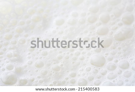 Over head close up full frame background detail view of frothy white milk creating bubbles, indoors. Macro still life view of liquid milk drink.