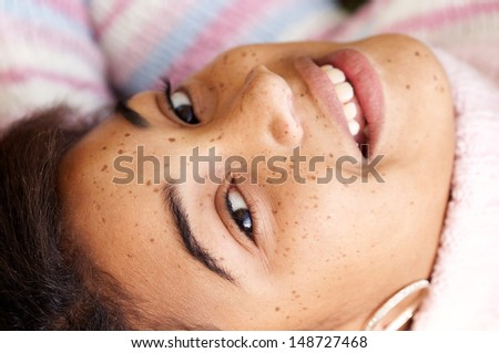 Over head close up portrait of a young black teenager relaxing outdoors, laying down and smiling at the camera, wearing a stripy jumper during a winter day. - stock photo