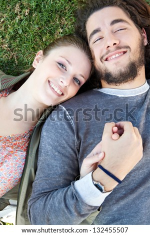 Over head close up portrait of a young bohemian couple laying down on green grass with their heads together and holding hands in a park, smiling.