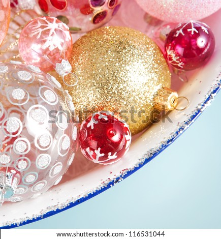 Over head close up view of a bunch of different size and design christmas balls in a silvery dish against a blue background. - stock photo