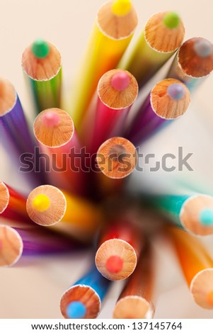 Over head close up view of a bunch of multiple colored drawing pencils isolated on a plain background. - stock photo