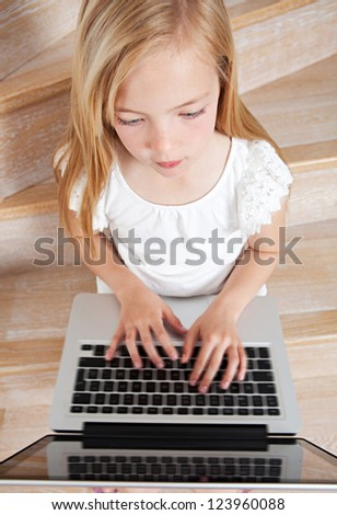 Over head close up view of a young girl child using a laptop computer while sitting on wooden steps at home. - stock photo
