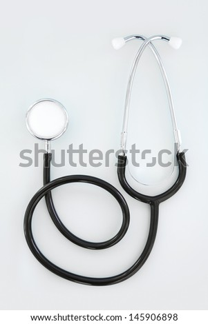 Over head full view of a doctors stethoscope laying down and curling isolated against a clean blue plain background with space around it.