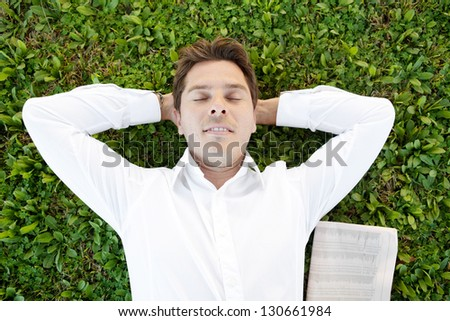 Over head portrait of a successful businessman laying down on green grass with his eyes closed and a financial newspaper next to him. - stock photo