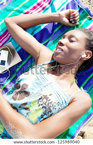 Over head portrait of an attractive african american woman listening to music while relaxing on a beach towel during her vacations. - stock photo
