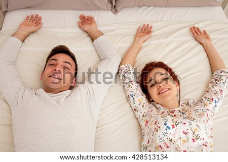 Over head portrait view of a young couple laying down relaxing, smiling and looking at camera, home interior. Boyfriend and girlfriend sharing a bed lying together being joyful, indoors bedroom. - stock photo