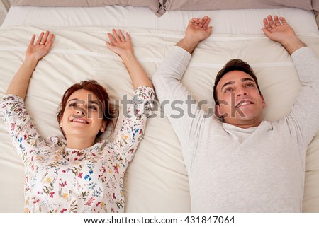 Over head portrait view of a young couple laying down relaxing, smiling and looking up in home interior. Boyfriend and girlfriend sharing a bed lying together being joyful, indoors bedroom. - stock photo