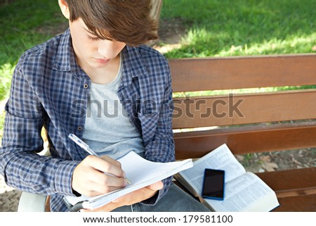 Over head portrait view of an attractive teenager student boy sitting on a wooden bench in a park with green grass, taking notes and doing his college homework during a sunny day, outdoors. - stock photo