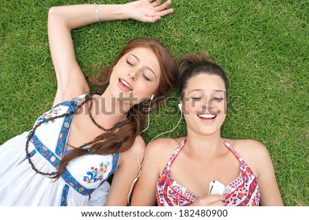 Over head portrait view of two young teenagers girls relaxing together while laying down on a park green grass during a break holiday listening to music and sharing headphones. Technology lifestyle. - stock photo