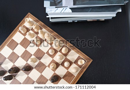 Over head still close up view of a traditional wooden game of chess being played on a dark wooden table in a home living room with a pile of books. Interior hobbies and interests.  - stock photo