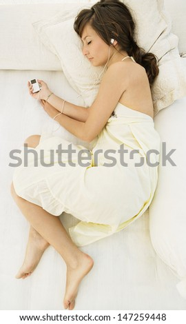 Over head view of a beautiful young woman laying down on an outdoors bed while on vacation and listening to music with her headphones, relaxing with her eyes closed.  - stock photo