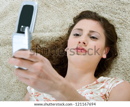 Over head view of a young and beautiful hispanic woman laying down on a furry carpet at home, using a cell phone in the living room,