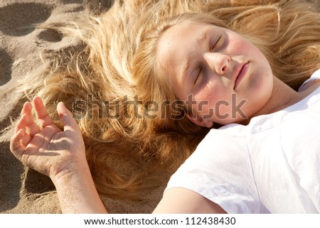 Over head view of a young girl laying down on a golden sand beach with her eyes shut while sunbathing. - stock photo