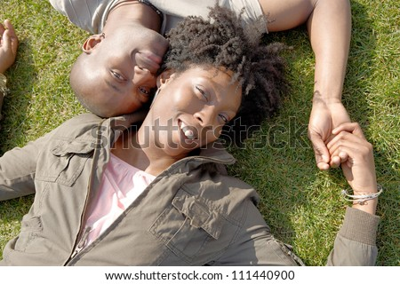 Over head view of an attractive black couple laying down on green grass, holding hands and smiling with their heads together.