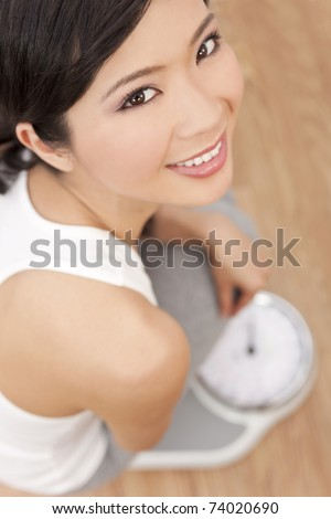 Over head view of happy & beautiful Oriental Asian Chinese woman weighing herself on scales at gym or health club