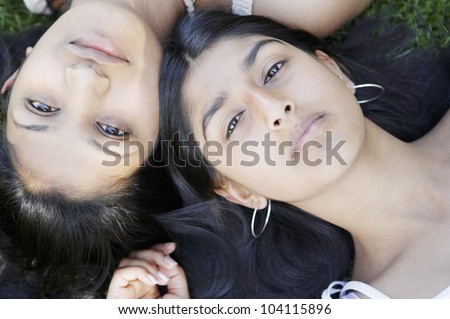 Over head view of two indian girls laying down on grass with their heads together.