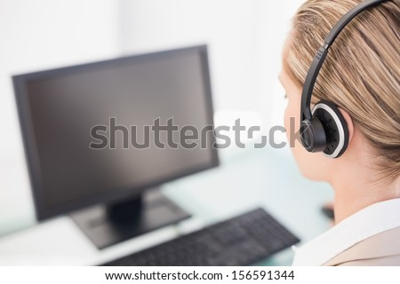 Over shoulder view of call center agent working in bright office - stock photo