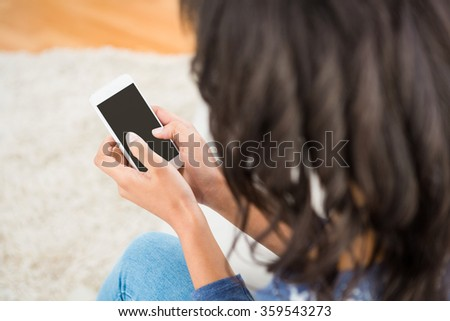 Over shoulder view of casual woman using her smartphone at home