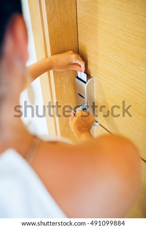 Over shoulder view of woman opening hotel door with electronic card.