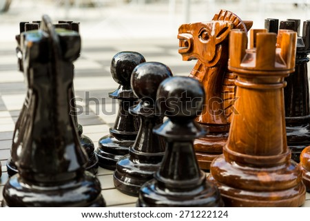 Over sized street chess figures on the board in the large city are lined up and ready to be placed on the playing board - stock photo