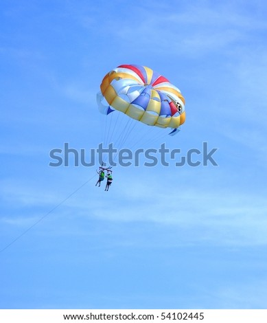 Over the sea on a parachute. A colored parachute over the dark blue sea.