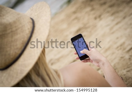 Over the shoulder shot of a woman using a phone sat on the beach - stock photo