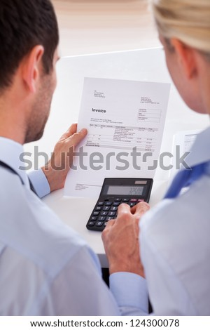 Over the shoulder view of a colleagues checking an invoice on a calculator - stock photo