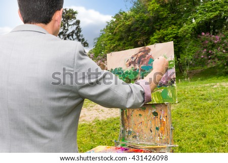 Over the shoulder view of a middle-aged fashionable male  painter working on a sketchbook painting a garden scene with flowers outdoors - stock photo