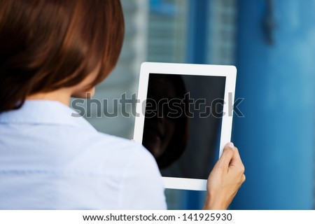 Over the shoulder view of a woman holding a tablet computer so that the blank black screen with copyspace is visible to the viewer