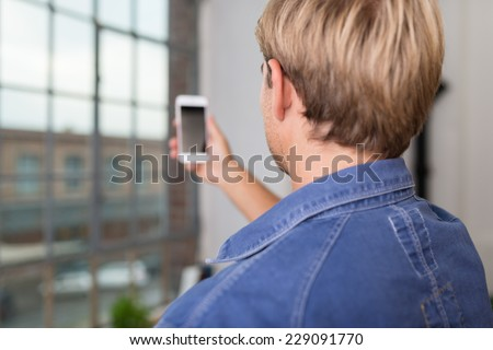 Over the shoulder view of a young blond man taking a selfie on his mobile phone posing for the camera - stock photo