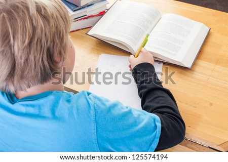 over the shoulder view of a young boy doing homework - stock photo