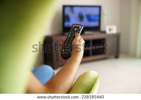 Over the shoulder view of girl sitting on sofa holding tv remote and surfing programs on television - stock photo
