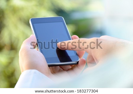 Over the shoulder view of young man using a mobile smart phone outdoor, blurred background - stock photo