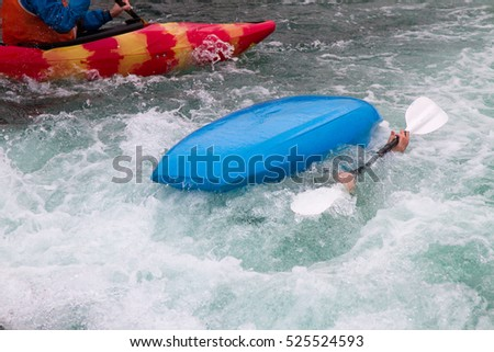 Over turned kayak boat in rough water showing two hands gripping onto the paddle