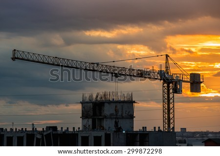 Over view of tower crane in construction machine a sky background, especially in dim light.