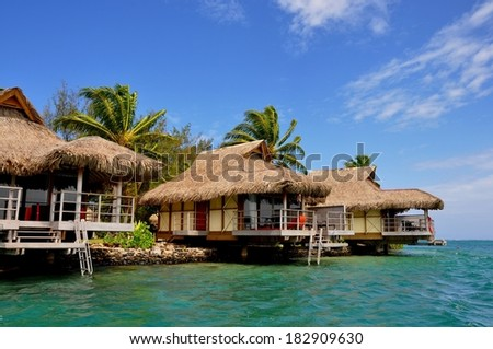 Over water bungalow in amazing green lagoon - stock photo