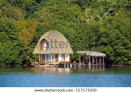 Over water bungalow with palm roof and lush tropical vegetation in background, Bocas del Toro, Caribbean sea, Central America, Panama - stock photo