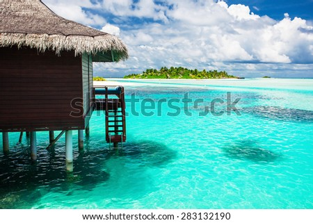 Over water bungalow with steps into amazing blue lagoon with island in distance - stock photo