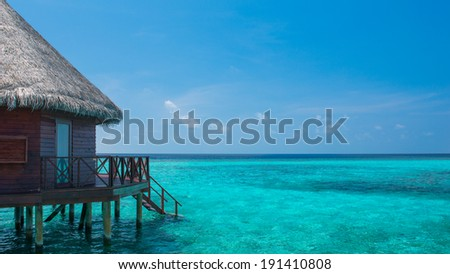 Over-water bungalows and blue lagoon, - stock photo