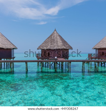 Over water  bungalows with stair descending into the sea. Turquoise color of the lagoon. Tropical island in the Indian Ocean. Luxury holiday.