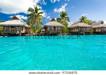 Over water bungalows with steps into amazing blue lagoon - stock photo