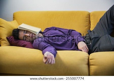 Over-worked, tired young man at home sleeping instead of working or studying, resting with head covered by open book - stock photo