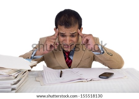 Overburdened Indian businessman with an expressions of despair, anxiety, hopelessness and breakdown holds his head amidst a pile of file folders. - stock photo