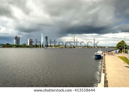 Overcast clouds over Daugava river with modern bridge, Riga, Latvia - stock photo