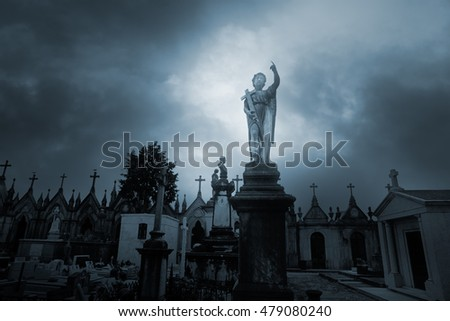 Overcast sad cemetery with an angel statue on the foreground