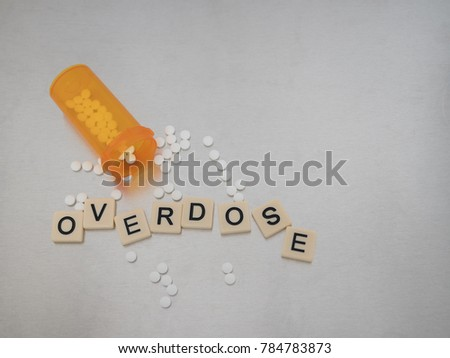 Overdose spelled with tile letters placed in a haphazard fashion with an open bottle of oxycodone tablets. Photographed from above on a stainless steel background. Image has copy space.